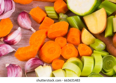 Texture of sliced vegetables on wooden table - potatoes, leeks, peppers, zucchini, garlic, tomatoes, celery