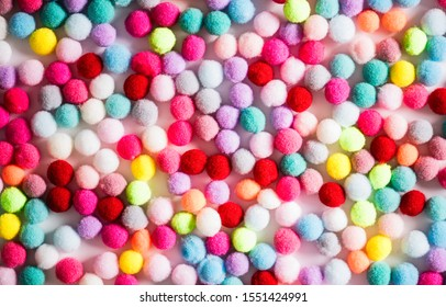 Texture of small colorful textile fluffy pompons on a white background. Flat lay. Creative.