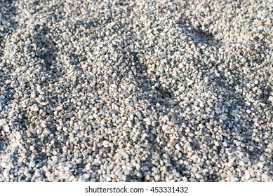 texture of small stones in a construction area. texture of pebbles with truck wheel trace, horizontal, nobody