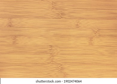 The texture of the smooth lacquered surface of the bamboo table.