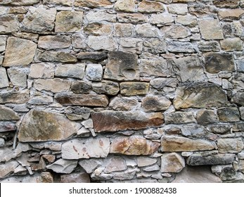 Texture with stacking sandy cobblestones. Light brownstones of different sizes. The structure of the old castle.