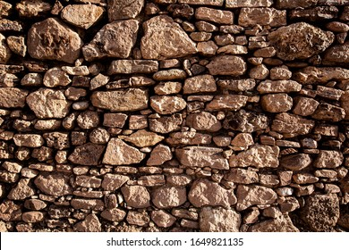 Texture of a stone wall. Old castle stone wall texture background. Brown, sienna large stones. Part of a stone wall, for background or texture