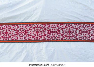 The texture of the surface of the white Yurt. Red national ornaments on the Yurt. Rest in Kyrgyzstan.