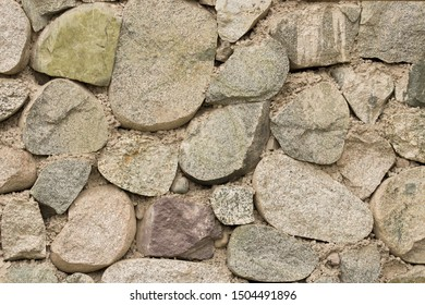 Texture of thick and strong wall of rough stones of various shapes. Stone wall background.