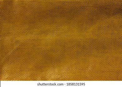 The texture of a thin nylon transparent fabric close-up in Fortuna Gold color. Pattern, background in color trend 2021