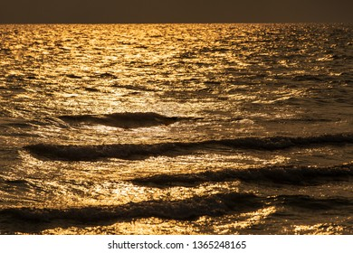 Texture of tropical sea water and wave in golden light of sunset.