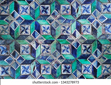 Texture of very old ceramic tiles in oriental style. Ancient pattern lined on the floor. Ruined vintage european tile in blue and green colors