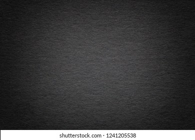 Texture of vintage dark black paper background with vignette. Structure of dense gray kraft cardboard with frame. Felt gradient backdrop closeup.