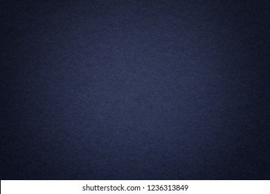 Texture of vintage dark denim paper background with vignette. Structure of dense navy blue kraft cardboard with frame. Felt gradient backdrop closeup.
