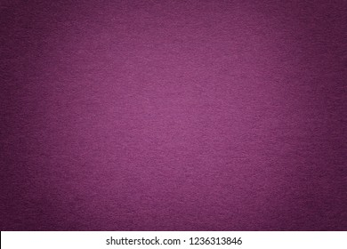 Texture of vintage dark purple paper background with vignette. Structure of dense magenta kraft cardboard with frame. Felt gradient backdrop closeup.