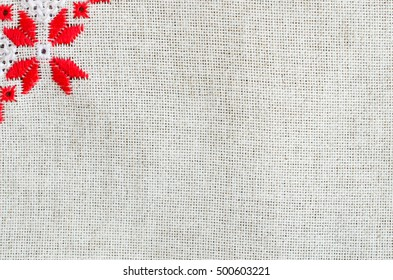 Texture of the vintage homespun linen textile. Background with element embroidery.