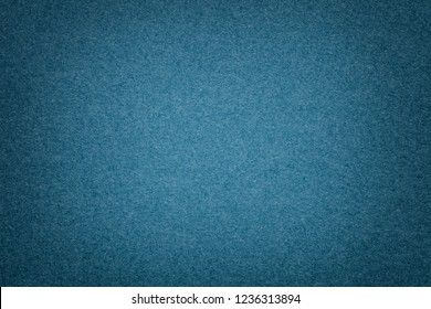 Texture of vintage navy blue paper background with vignette. Structure of dense dark denim kraft cardboard with frame. Felt gradient backdrop closeup.