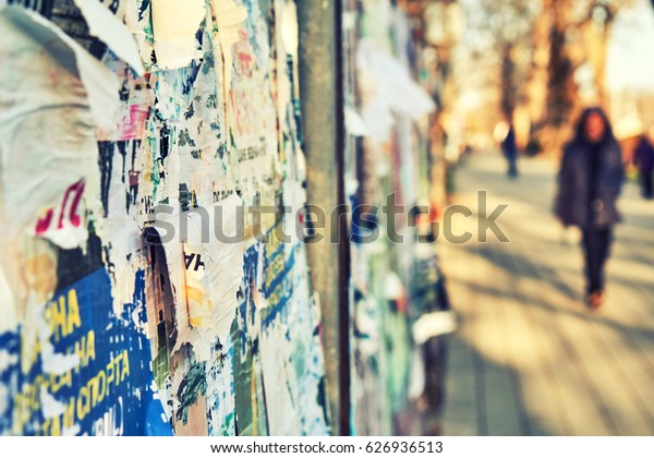The texture of a wall with torn posters and ads. Bright abstract background ideal for any design