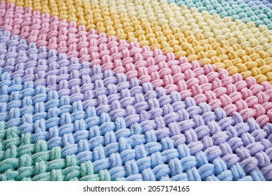 The texture is a warm bright plaid made of multicolored terry loop yarn. Thread loops pattern. A cozy pastime for a hobby