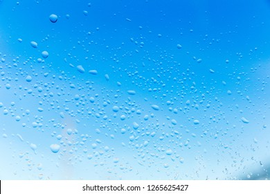 Texture of water droplets on glass window in fall or winter setting. Blurry background with water drops in focus.