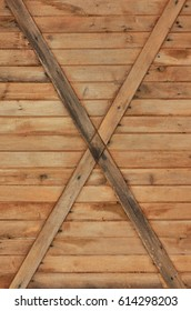The texture of weathered wooden wall.   Texture of an old fence of horizontal orange wooden planks with cross-boards