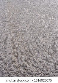 Texture of wet sand on a beach during low tide.