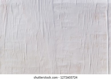 Texture of wet white folded paper on an outdoor poster wall, crumpled paper background. - Shutterstock ID 1272603724