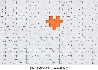 The texture of a white jigsaw puzzle in an assembled state with one missing element forming an orange space