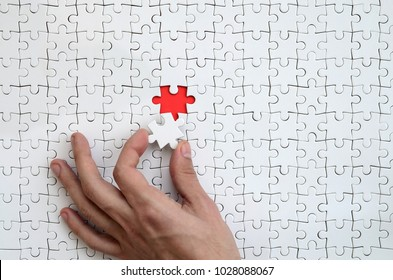 The texture of a white puzzle puzzle in the assembled state with one missing element that the male hand puts in