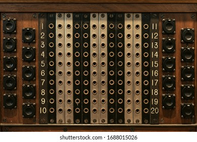 The texture of the wood panel of the old switchboard with buttons and holes.
