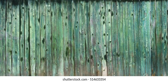Texture wooden fence with vertical green boards and faded paint background