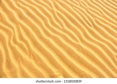 Texture of yellow desert sand dunes. Can be used as natural background