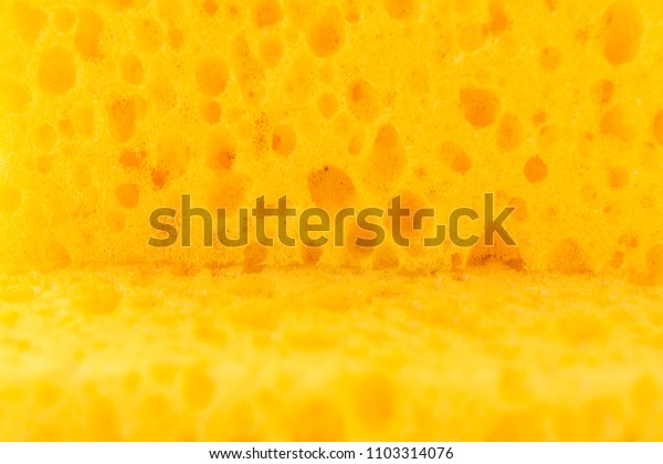 texture yellow foam rubber, synthetic sponge with large pores, selective focus, close-up abstract background