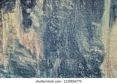 the textured abstract background with an indistinct pattern of blue and cream shades with smudges and with effect of aging