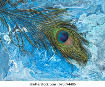 Textured background art created by pouring vibrantly colored acrylics with peacock feathers