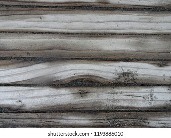 Textured background closeup showing wet sand on weathered boards at Petone Beach Wellington harbour New Zealand