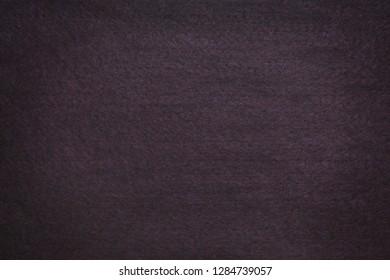 Textured background of dark brown felt with vignette