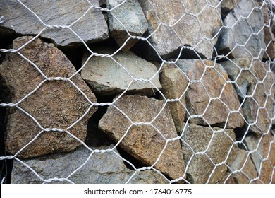 Textured background, gabion wall caged stones close-up. Building object.