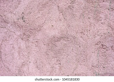 Textured background The outer surface of the wall of a residential house is plastered. Rough texture fancy patterns of ointment on external plastering work of pink color