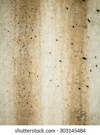 Textured background of two dirty brown rust stains running down a grey concrete wall