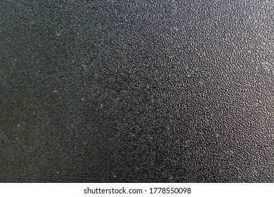 textured black Hammerite paint on metal surface.
