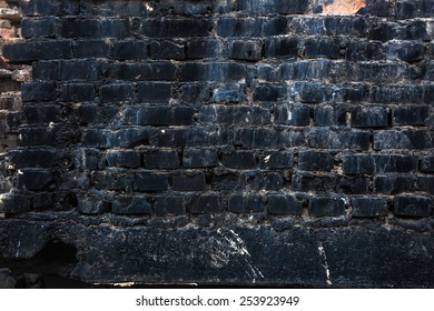Textured brick wall after a fire in black
