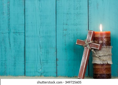 Textured candle burning and rugged wooden cross with rope by antique rustic teal blue wooden background; Easter, Christmas, Memorial Day and religious background with painted copy space