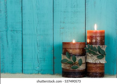 Textured candles with rope and leaves burning by antique rustic teal blue wooden background; blank spa sign background with copy space