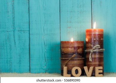Textured candles with rope and the word LOVE burning by antique rustic teal blue wooden background; blank holiday sign background with copy space