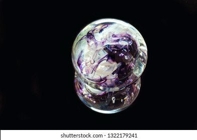 textured glass paperweight and reflection isolated against black