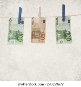 Textured old paper background with banknotes euro on a clothesline
