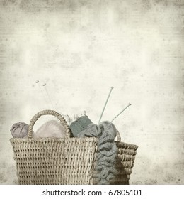 textured old paper background with knitter's basket with unfinished work and yarns
