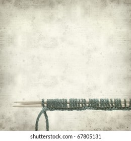 textured old paper background with knitting needles and blue yarn