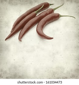 textured old paper background with red hot chili pepper