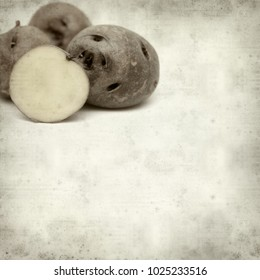 textured old paper background with small dark Canary Islands potatoes  papa bonita, i.e.e pretty potato, old variety of potatoes