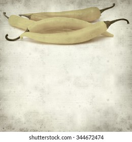 textured old paper background with yellow chilli pepper