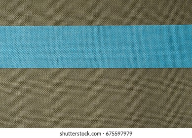 A textured, olive burlap background with a blue burlap ribbon stripe