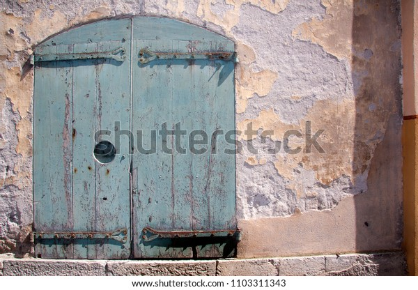 textured stone wall with pastel coloured doors