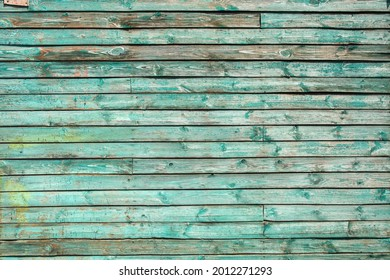 textured surface made of old wood planks with shabby weathered green paint